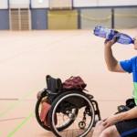 David sitzt am Spielfeld in der Sporthalle und trinkt Wasser.