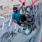David fährt hoch in eine steile Kurve im Skatepark.