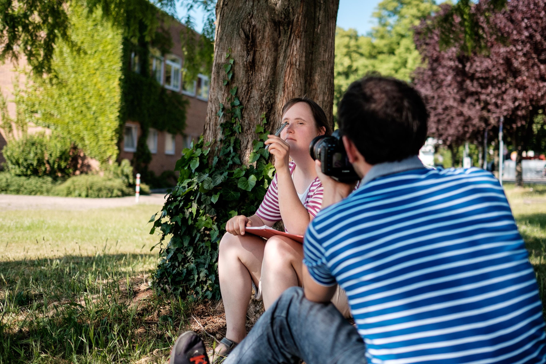 Andersmacherin Carina sitzt unter einem Baum und wird dabei gefilmt, wie sie einen Brief schreibt.