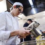 Fabio quetscht in der Küche Kartoffeln mit einer Presse zu Kartoffelbrei.