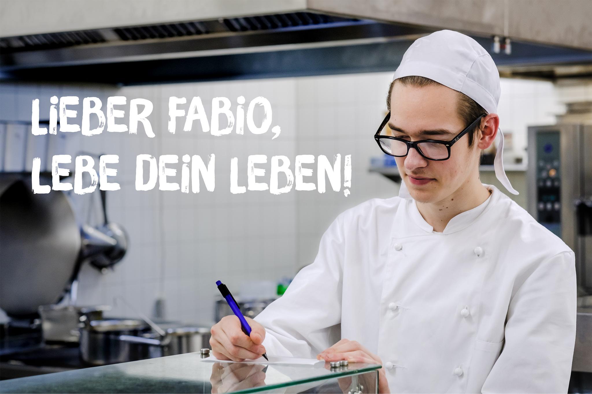 """Fabio schreibt in der Küche etwas auf einen Zettel. In Schrift steht daneben: """"Lieber Fabio, lebe dein Leben!"""""""
