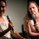 Carina sitzt mit einer anderen Frau auf der Bühne und hält ein Mikrofon