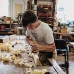 David steht an der Werkbank und bearbeitet mit dem Hobel ein Stück Holz.