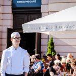 Fabio steht draußen im Koch-Outfit auf der Terrasse des Museumscafés. Die Sonne scheint. Im Hintergrund sieht man Menschen an Café-Tischen und einen Sonnenschirm mit der Aufschrift: